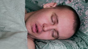 Close-up shot of young man in bed at home sleeping.  Stock Photo