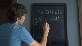 Close Up shot of a young man that is drawing a `Dream big, set goals, take action` message on a chalkboard.  stock footage