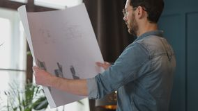 Close up shot of young man hands engineer opening the paper and checking the construction drawings in the architecture. Office. man hipster standing faces to stock footage