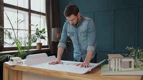 Close up shot of young man hands engineer opening the paper and checking the construction drawings in the architecture. Office stock footage