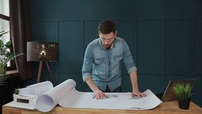Close up shot of young man hands engineer opening the paper and checking the construction drawings in the architecture. Office. man hipster standing faces to stock video