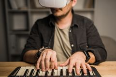 Man in vr goggles using MPC pad. Close-up shot of young man in vr goggles using MPC pad Royalty Free Stock Photography