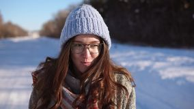 Close up shot of young pretty woman walking outdoor in sunny winter day. stock footage