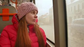 Close-up shot of a young sad woman traveling by bus on a dull rainy day. She looking out the wet window and breathing stock video