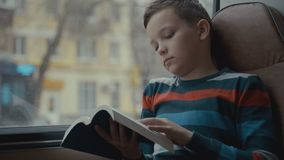 Close-up shot of a young schoolboy traveling by bus through city and reads a book. Close-up shot of a young schoolboy traveling by bus through city and reads a stock video