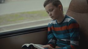 Close-up shot of a young schoolboy traveling by bus through city and reads a book. Close-up shot of a young schoolboy traveling by bus through city and reads a stock footage