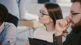 Close-up shot of young smiling beautiful female office manager talks at multiethnic company staff meeting, work process. Attractive elegant confident designer stock footage