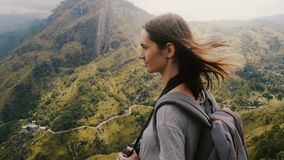 Close-up shot of young tourist woman with backpack and camera enjoying wind in her hair at amazing mountain scenery. Peaceful female traveler meditating in Sri stock video footage