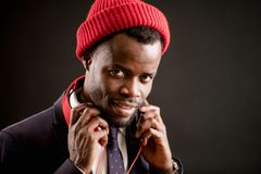 Young handsome talented Afro singer in headphones and red cap. Close up shot of young unshaven handsome talented Afro singer in headphones and red cap on an Royalty Free Stock Photo