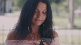 Close up shot of young woman listening music in the headphone while using smartphone in the city. Portrait shot. Close up of young woman listening music in the stock footage