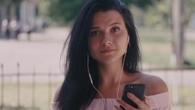 Close up shot of young woman listening music in the headphone while using smartphone in the city. Portrait shot. Close up of young woman listening music in the stock video footage