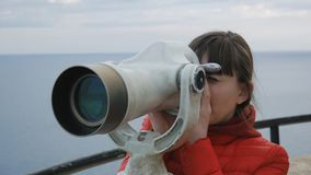Close-up shot of young woman in red bubble jacket looking into the telescope from the observation deck on the sea. Background stock video