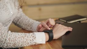 Close up shot of young woman`s hands who uses a smart watches for business work stock video footage