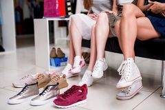 Close-up shot of young women trying on different footwear while sitting in a shoe store.  stock photography