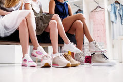 Close-up shot of young women trying on different footwear while sitting in a shoe store.  Royalty Free Stock Photo