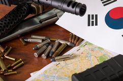 Close up of a shotgun and a revolver, cartridge belt with bullets with North Korean flag on a map, on wooden table Royalty Free Stock Image