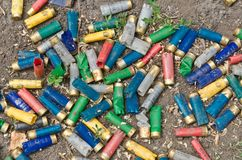 Close-up of the shotgun shells on the ground. A lot of utilized shotgun collets are heaped on the soil after shooting Royalty Free Stock Images