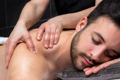 Close up shoulder massage on young man. Close up of physiotherapist dong healing shoulder massage on young man Royalty Free Stock Photography