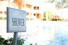 Close up of shower sigh with sunny background. Grey Shower sigh near swimming pool in summer day. Shower pointer. signboard of pla. Ce to take a shower royalty free stock images