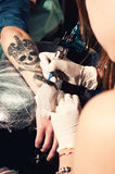 Close up showing process of making a tattoo on a hand, black skull with crown Stock Photos