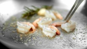 Close up on a shrimps fry on a frying pan with a garlic and rosemary. stock footage