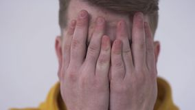 Close-up of a shy young man looking at the camera from behind fingers covering face with his hands. Concept of hiding