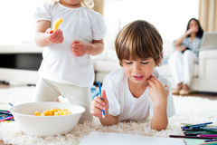 Close-up of siblings eating chips and drawing Stock Photo