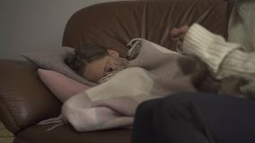 Close-up of sick caucasian girl lying under blanket at home. Sad child has fever. Young mother checking daughter`s. Temperature on thermometer. Concept of stock footage