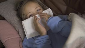 Close-up of sick caucasian girl sneezing. Sad child lying under blanket at home with fever. Concept of health, illness. Sickness, common cold, treatment stock video footage