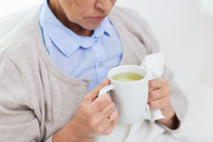 Close up of sick senior woman drinking tea at home Royalty Free Stock Photography