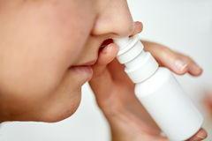 Close up of sick woman using nasal spray. Healthcare, flu, rhinitis, medicine and people concept - close up of sick woman using nasal spray Stock Image