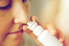 Close up of sick woman using nasal spray. Healthcare, flu, rhinitis, medicine and people concept - close up of sick woman using nasal spray Royalty Free Stock Photo