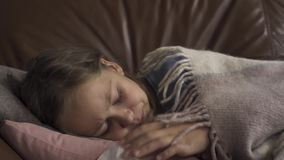 Close-up of sick young caucasian girl coughing and blowing nose while lying under blanket at home. The child has fever. Close-up of sick young caucasian girl stock video footage