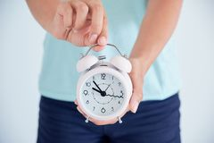 Close up of a sick young woman with a clock in her hands. the concept of regulation of the menstrual cycle. time to take care of h. Closeup ill young woman on stock image