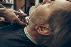 Close-up side back view handsome senior bearded caucasian man getting beard grooming in modern barbershop. Hairdresser serving client, making beard haircut Stock Images