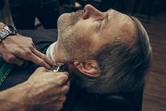 Close-up side back view handsome senior bearded caucasian man getting beard grooming in modern barbershop. Hairdresser serving client, making beard haircut Stock Photography