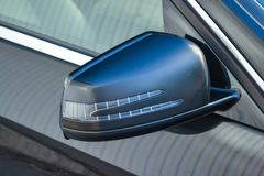 Close-up of the side left mirror with turn signal repeater and window of the car body black SUV on the street parking after royalty free stock images