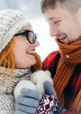 Close-up side portrait of the cheerful smiling couple holding hands during winter time. Beautiful redhead woman is stock image