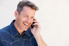 Close up older man laughing and talking on mobile phone Royalty Free Stock Image
