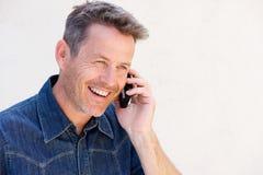 Close up older man laughing and talking on mobile phone. Close up side portrait of older man laughing and talking on mobile phone royalty free stock image