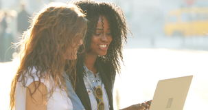 The close-up side portrait of smiling multiethnic girlfriends texting, chatting and surfing the net using the laptop. While sitting on the road stock footage