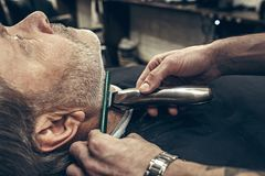 Close-up side profile view portrait of handsome senior bearded caucasian man getting beard grooming in modern barbershop. Close-up side profile portrait of Royalty Free Stock Photography