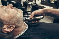 Close-up side profile view portrait of handsome senior bearded caucasian man getting beard grooming in modern barbershop. Close-up side profile portrait of Royalty Free Stock Photos