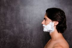 Close up side profile shot of face of concentrated virile mature. Harsh mulatto hispanic man with white foam on his face, isolated on grey background, so hot Stock Photo