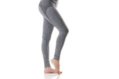 Close up side sexy view of woman legs stretching the muscles of the foot in gray sports thermal underwear with pattern. Stock Photography