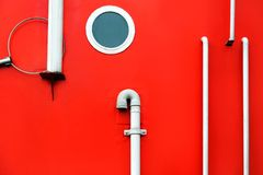 Board portholes red side ship fragment white background old close-up orange handrails. A close-up of side of ship with a porthole and handrails. Board the red royalty free stock image