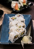 A close-up side shoot of Uramaki sushi rolls with fresh salmon, avocado and philadelphia cheese, covered with sesame seeds Stock Image