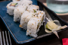 A close-up side shoot of Uramaki sushi rolls with fresh salmon, avocado and philadelphia cheese, covered with sesame seeds Stock Images