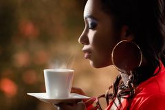 Attractive African woman smelling hot cup of coffee. Royalty Free Stock Photos