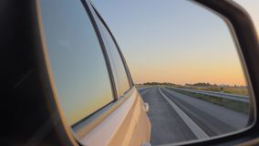 Close-up of the side view car mirror at sunset. Car drives on the highway stock video